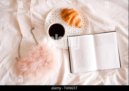 Cup of coffee with pie, open book and stylish bag closeup. Top view. - Stock Photo