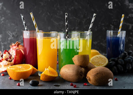 a set of cool fresh squeezed juices or cocktails in a glasses made from orange, kiwi, lemon, grapes, pomegranate - Stock Photo