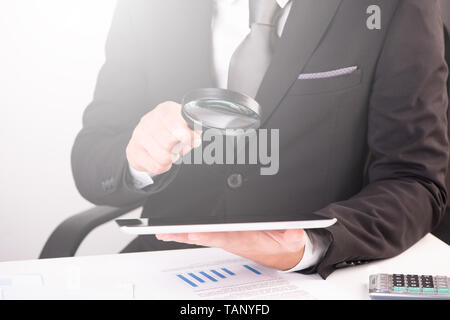 Businessman holding magnifying glass and digital tablet close up - Stock Photo