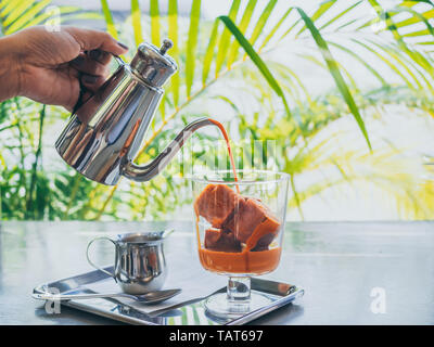 Hand pouring Thai milk tea from stainless steel jug on Thai tea ice cubes in glass with milk in small jug on stainless steel tray on concrete table. - Stock Photo
