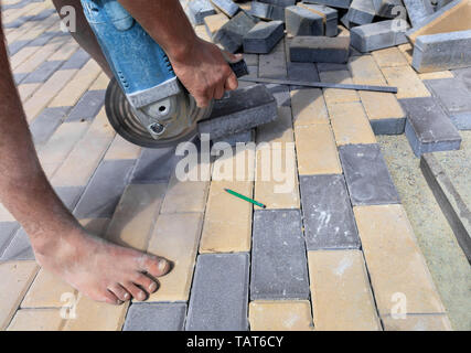 The worker cuts a bar of paving slabs for the final laying on the terrace on a city street at noon. - Stock Photo