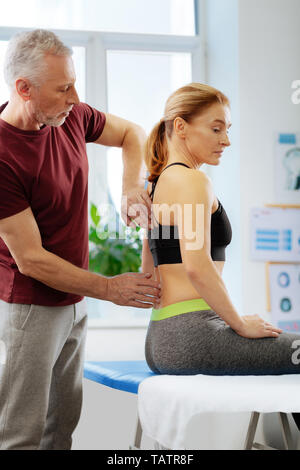 Skilled therapist. Nice aged man standing behind his patient while doing a professional massage for her - Stock Photo