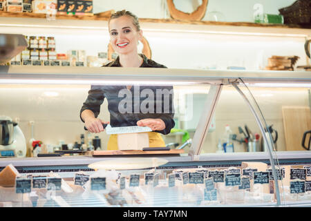 Women selling cheese at counter in a supermarket - Stock Photo