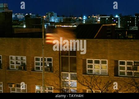 American flag, Stars and Stripes, waving in the wind during a calm and quiet night in the Bronx, NY, USA - Stock Photo