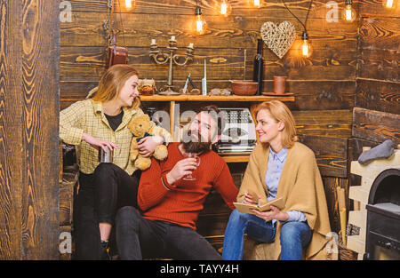 Girl holding teddy enjoys evening with parents. Bearded man sitting between his wife and child in countryside house. Beautiful mom and daughter looking at each other and smiling, family fun concept. - Stock Photo