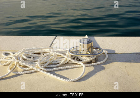 White rope and mooring pillar by the blue sea, detail in yacht marina - Stock Photo