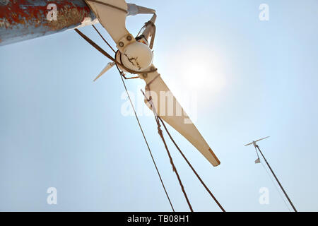 Looking up small broken wind turbine, strong midday sun shining on the sky. - Stock Photo