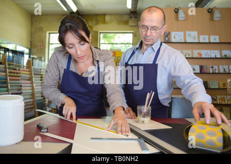 man and woman making wooden frame - Stock Photo