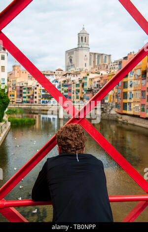 Man looking at view from Eiffel Bridge (Pont de les Peixateries Velles) over the Onyar River at the Girona Cathedral and multi coloured houses in Giro - Stock Photo