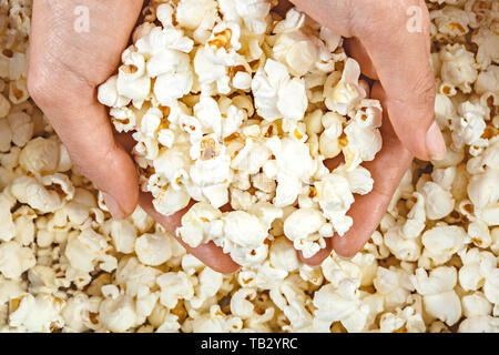 High angle view of hands contain popcorn from a bowl. - Stock Photo