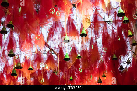 Golden bells with greeting lucky word on red ribbon at Kalighat Kali Mandir Temple Kolkata. Pilgrims people wish and hang it on rope for pray. Merry c - Stock Photo