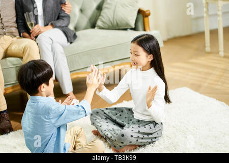 two cute little asian kids brother and sister sitting on carpet playing game with parent sitting on sofa in the background - Stock Photo