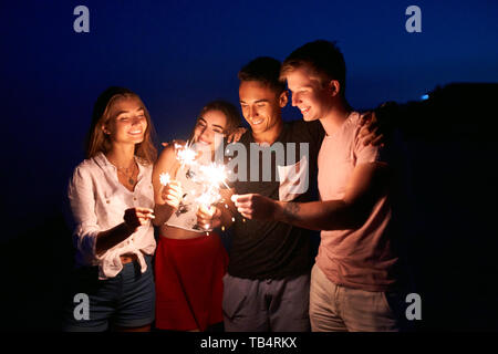 Friends walking, dancing and having fun during night party at the seaside with bengal sparkler lights in their hands. Young teenagers partying on the - Stock Photo