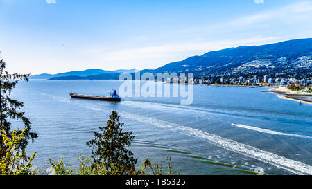 Cargo ship leaving the Port of Vancouver and steaming into Burrard Inlet. Viewed from the Lions Gate bridge at Stanley Park, British Columbia, Canada - Stock Photo