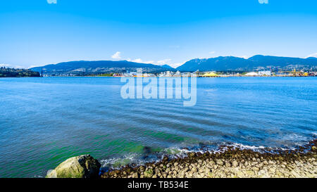 View of the North Shore of the Vancouver Harbor with the Lions Gate Bridge in the distance. Viewed from the Stanley Park Seawall in Vancouver, Canada - Stock Photo