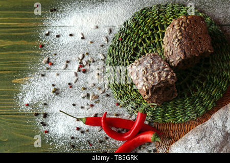 Fresh tasty bread with spices on wooden table - Stock Photo