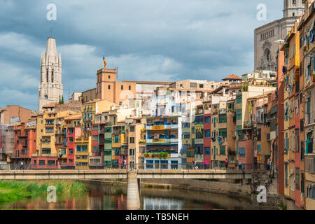 Collegiate Church of Sant Felix (Pujada de Sant Feliu) and multi colored houses from bridge on the Onyar River, Girona, Spain - Stock Photo