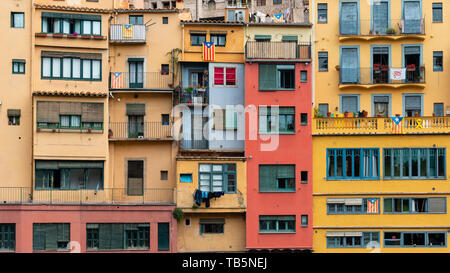 Multi colored houses on the bank of the Onyar River, Girona, Spain. Estelada Blava, flag of Catalonian independence, displayed on balconies and window - Stock Photo
