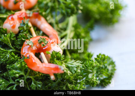 Shrimps prawns in skewer sticks seafood cooked with ketchup sauce herbs and spices on curly parsley background / Close up shellfish shrimp boiled - Stock Photo
