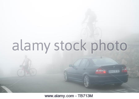 Cyclist crossing road in front of the statue for Tour de France winner Octave Lapize at the Col du Tourmalet in thick mist in the Pyrenees, France - Stock Photo