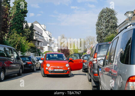 Strasbourg, France - Apr 4, 2017: Fiat 500 red car with open door blocking entire street in Strasbourg in residential area - Stock Photo