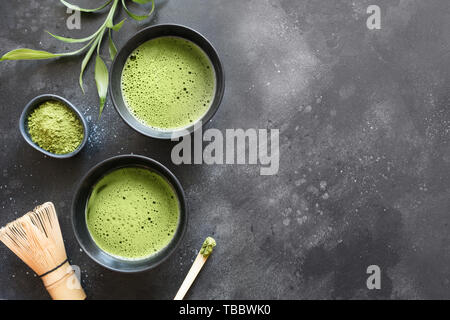 Still life with Japanese matcha green tea in bowl with accessories on black table. View from above. Space for text. - Stock Photo