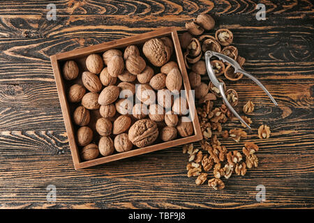Box with tasty walnuts and nutcracker on wooden table - Stock Photo