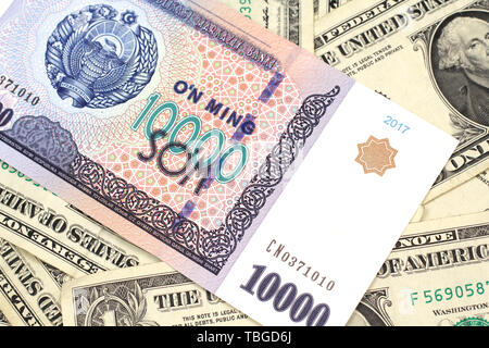 A close up image of a ten thousand Uzbek som bank note on a background of United States one dollar bills in macro - Stock Photo