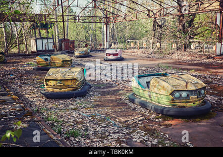 abandoned bumper cars in ruined amusement park in Pripyat city, Exclusion zone of Chernobyl, Ukraine, Eastern Europe - Stock Photo