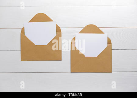 Mockups of invitations on white wooden background - Stock Photo