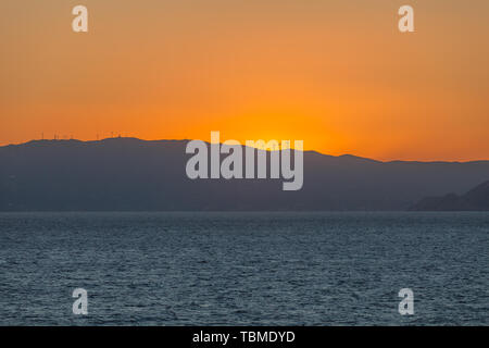 Colorful sky behind the profile of an island carpeted with wind turbines - Stock Photo