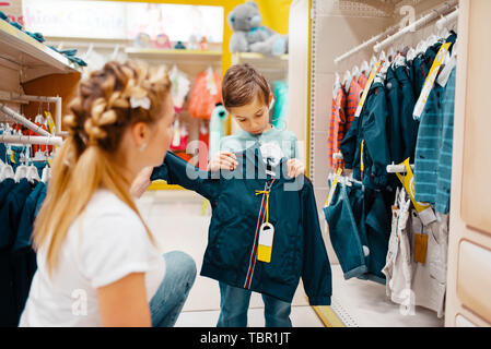 Mother with her boy choosing clothes in kids store - Stock Photo