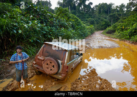 4X4 vehicle stuck in a deep muddy pothole on Linden-Lethem Road in Guyana South America - Stock Photo