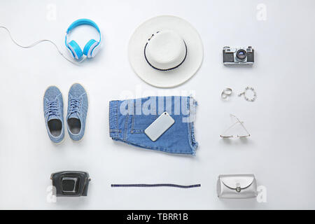 Set of clothes, accessories and photo camera on white background - Stock Photo