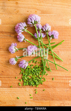 Chopped chives with Flowers on old kitchen table. - Stock Photo