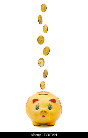 A string of coins falling down into a piggy bank against a white background - Stock Photo
