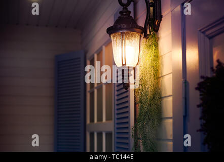 Vintage iron lantern on the wall outdoor in the evening. Exterior design elements. - Stock Photo