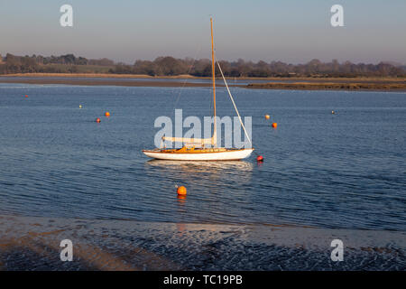 Small sailing yacht moored in winter on River Deben, Waldringfield, Suffolk, England, UK - Stock Photo