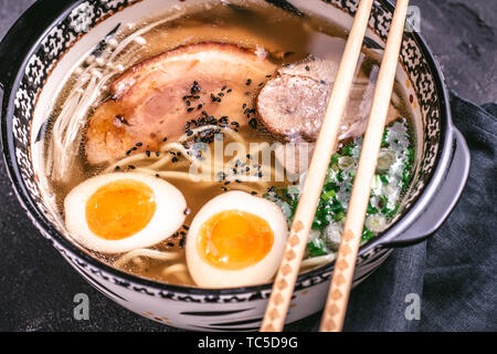 Udon Noodles in Japanese Ramen Soup with Pork, Eggs and Scallion on Dark Background - Stock Photo