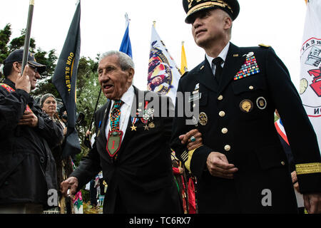 Pointe Du Hoc, France. 05th June, 2019. U.S. Gen. Paul M. Nakasone, commander of Cyber Command, right, escorts Native American WWII veteran Charles Shay to the Charles Shay memorial ceremony at Omaha Beach on the anniversary of the D-Day invasion June 5, 2019 in Pointe du Hoc, Normandy, France. Thousands have converged on Normandy to commemorate the 75th anniversary of Operation Overlord, the WWII Allied invasion commonly known as D-Day. Credit: Planetpix/Alamy Live News - Stock Photo