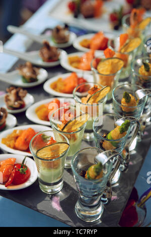 Spoons and glasses with seafood snacks on banquet table - Stock Photo