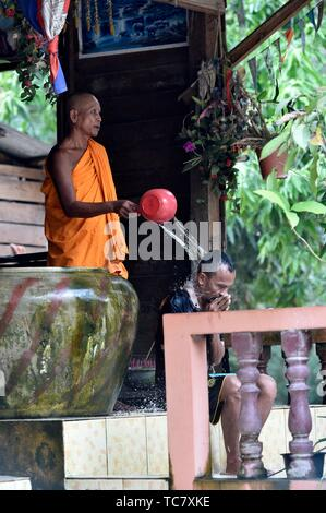 Buddhist monk water blessing man,Siem Reap,Cambodia,South east Asia. - Stock Photo