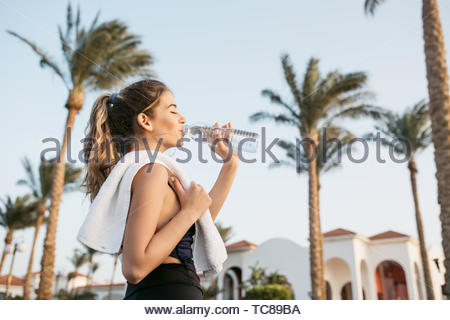 Portrait attractive young woman in sportswear drinking water from bottle on palms and sky background. Tropical city, sunny morning, relaxing with closed eyes, workout - Stock Photo