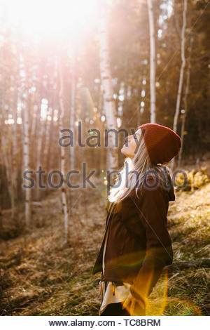 Serene woman basking in sunlight, hiking in woods - Stock Photo