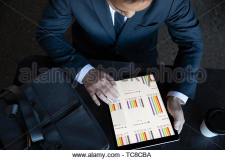 View from above businessman looking at data on digital tablet - Stock Photo