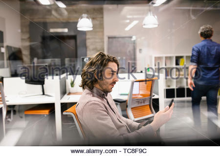 Businessman using smart phone in office - Stock Photo