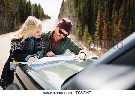 Couple looking at map on hood of car at sunny roadside - Stock Photo
