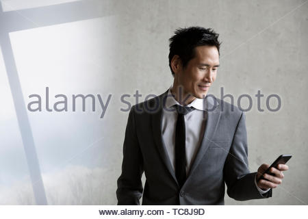 Smiling businessman using smart phone - Stock Photo