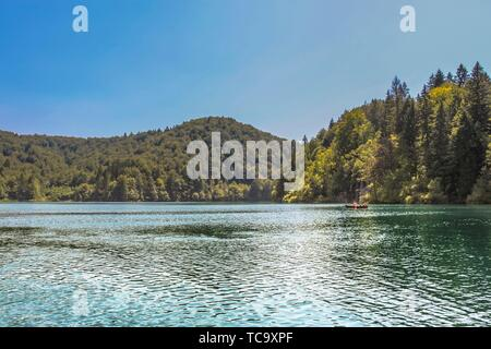 Lika-Senj County, Karlovac County, Croatia - 2013: Tourist taking a boat ride on the lakes in Plitvice Lakes National Park. - Stock Photo