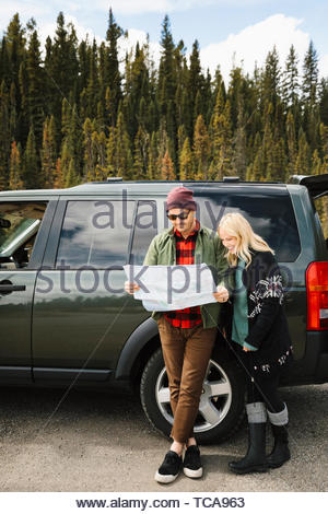 Couple with map standing outside SUV at roadside - Stock Photo